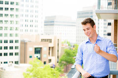 Handsome man waving from balcony and enjoying drink Stock Photos