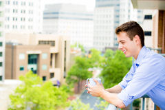 Handsome man waving from balcony and enjoying drink Stock Images