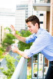 Handsome man waving from balcony and enjoying drink Royalty Free Stock Photos
