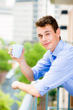 Handsome man waving from balcony and enjoying drink Royalty Free Stock Image