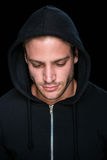 Handsome man wearing a black hoodie. On black background Royalty Free Stock Images