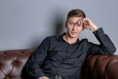 Handsome man wearing black shirt sitting on the leather sofa. Comfort and relaxation stock photography