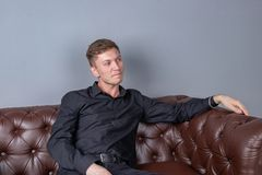 Handsome man wearing black shirt sitting on the leather sofa. Comfort and relaxation royalty free stock image
