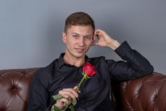Handsome man wearing black shirt sitting on the leather sofa holding a rose and getting ready romantic date royalty free stock photos