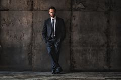 Handsome man wearing black suit on a grunge background. Studio portrait of a handsome man wearing black suit on a grunge background royalty free stock photography