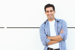 Handsome man wearing blue plaid shirt with arms crossed. On white urban background Stock Photos
