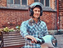 Handsome man wearing casual clothes in a helmet, riding on a retro classic scooter, along the old streets in a Europe. A handsome man wearing casual clothes in Royalty Free Stock Photography