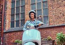 Handsome man wearing casual clothes in a helmet, riding on a retro classic scooter, along the old streets in a Europe. A handsome man wearing casual clothes in Royalty Free Stock Image