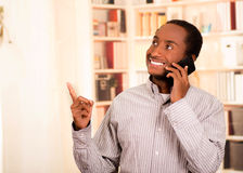 Handsome man wearing casual clothes talking on mobile phone while pointing upwards, white bookshelves background Royalty Free Stock Photography