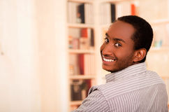 Handsome man wearing casual clothes turning head around smiling to camera, white bookshelves background Royalty Free Stock Images