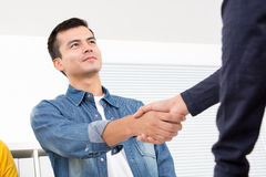 Handsome man wearing casual jean shirt making handshake in the o. Ffice Stock Image