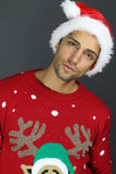 Handsome man wearing a Christmas hat and sweater. Over a gray background Stock Photography