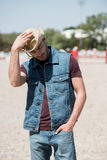 Handsome man wearing cowboy hat and denim vest standing on ranch Royalty Free Stock Images
