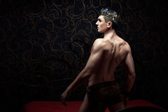 Handsome man wearing crown standing on a bed. Royalty Free Stock Photos