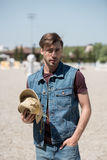 Handsome man wearing denim vest, holding cowboy hat and looking at camera Royalty Free Stock Photo