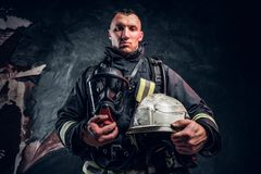 A handsome man wearing a fire suit holding an oxygen mask and helmet, looking at a camera. Studio photo against a dark textured wall royalty free stock images