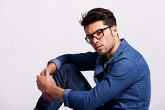 Handsome man wearing glasses sitting Stock Images