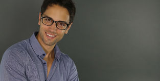 Handsome man wearing glasses smiling. Over a gray background Stock Images
