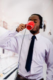 Handsome man wearing headphones with microphone, white striped shirt and tie, drinking from coffee mug, business concept.  Stock Images