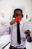 Handsome man wearing headphones with microphone, white striped shirt and tie, drinking from coffee mug, business concept.  Stock Image