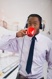 Handsome man wearing headphones with microphone, white striped shirt and tie, drinking from coffee mug, business concept.  Royalty Free Stock Image