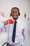 Handsome man wearing headphones with microphone, white striped shirt and tie, holding coffee mug smiling to camera. Business concept Royalty Free Stock Photos