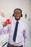 Handsome man wearing headphones with microphone, white striped shirt and tie, holding coffee mug smiling to camera. Business concept Royalty Free Stock Photo