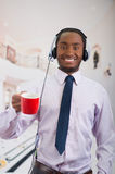 Handsome man wearing headphones with microphone, white striped shirt and tie, holding coffee mug smiling to camera. Business concept Stock Photo