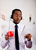Handsome man wearing headphones with microphone, white striped shirt and tie, holding coffee mug, surprised facial. Expression, business concept Royalty Free Stock Photos