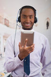 Handsome man wearing headphones with microphone, white striped shirt and tie, posing holding tablet in hand, smiling Stock Photography