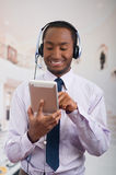 Handsome man wearing headphones with microphone, white striped shirt and tie, posing holding tablet in hand, smiling Royalty Free Stock Images