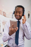 Handsome man wearing headphones with microphone, white striped shirt and tie, posing holding tablet in hand, smiling Royalty Free Stock Photos