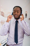 Handsome man wearing headphones with microphone, white striped shirt and tie, posing interacting working for camera Royalty Free Stock Photography