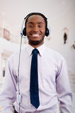 Handsome man wearing headphones with microphone, white striped shirt and tie, posing interacting working for camera.  Stock Image