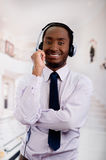 Handsome man wearing headphones with microphone, white striped shirt and tie, posing interacting working for camera Royalty Free Stock Photo