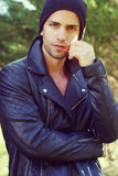 Handsome man wearing a leather jacket and a hat Stock Photo