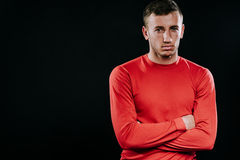 Handsome man wearing red sportswear and posing after exercises on dark background. Healthy inspirational fitness lifestyle, sport. Caucasian sportsman wearing Royalty Free Stock Image