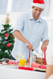 Handsome man wearing a santa hat and carving roast chicken royalty free stock image