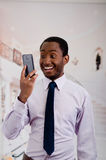 Handsome man wearing shirt and tie holding up mobile phone posing while taking a selfie Stock Photography