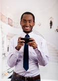 Handsome man wearing shirt and tie holding up mobile phone writing text message Stock Photo