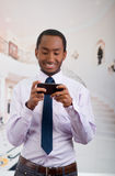 Handsome man wearing shirt and tie holding up mobile phone writing text message Royalty Free Stock Photography