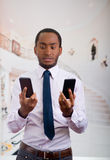 Handsome man wearing shirt and tie holding up two mobile phones with stressed facial expression.  Stock Images