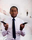 Handsome man wearing shirt and tie holding up two mobile phones with stressed facial expression.  Stock Photos