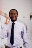 Handsome man wearing shirt and tie standing in lobby area talking on mobile phone, business concept Stock Photos
