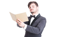 Handsome man wearing tuxedo and bowtie looking at catalogue Stock Photos