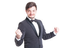 Handsome man wearing tuxedo and bowtie making success gesture Royalty Free Stock Photo