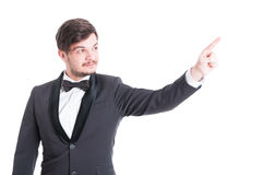 Handsome man wearing tuxedo and bowtie pointing stock image