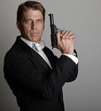 Handsome man in tuxedo with gun Stock Image