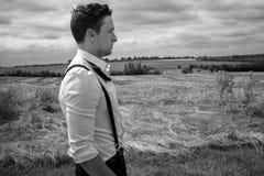 Man wearing tuxedo walks through field in countryside stock photography