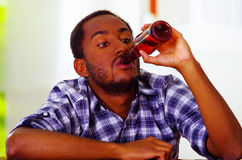 Handsome man wearing white blue shirt sitting by bar counter lying over desk drinking from brown beer bottle, drunk Royalty Free Stock Photography